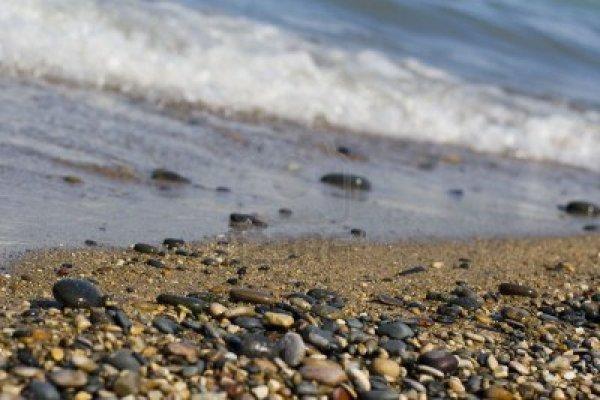 948427-las-olas-rompiendo-sobre-la-arena-y-de-cantos-rodados-de-playa